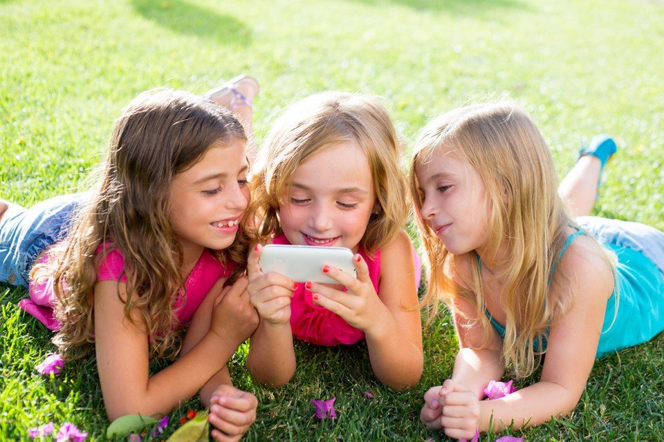 девочки на газоне смотрят ролик на смартфоне